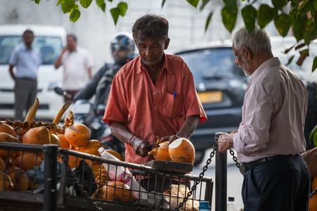 The man sells from the cart orange drinking cocoes on the street of the city. Sri Lanka, Colombo, on January 21, 2017