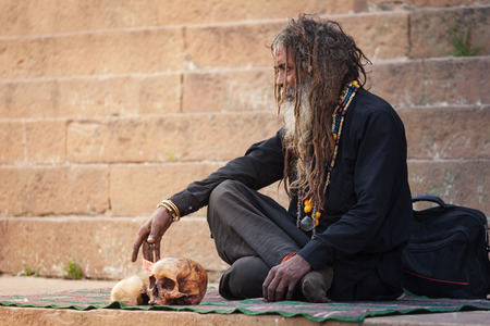 The Indian tramp of the sadhu with the tousled dreadlocks sits near the real human skulls on the river bank Ganges in the city of Varanasi on February 6, 2014