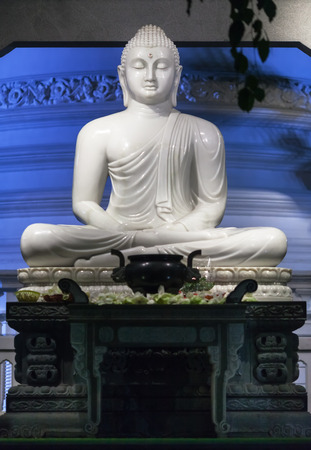 The big statue of white Buddha made of marble, located on a temple Gangaramaya altar in Colombo. Stock Photo