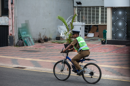 The Sri-lankian police officer in a form and a reflecting vest, goes by bicycle on one of streets of capital of Sri Lanka, Colombo, on January 21, 2017