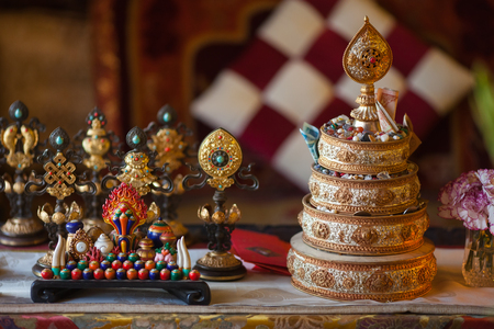 The little table with the ritual mandala filled with rice and gifts and signs of happines, faces an altar in the Buddhist temple. Stock Photo
