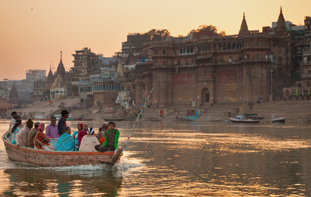 The boat with indian pilgrims floats across Ganges along the embankment of Varanasi at sunset. India, Uttar Pradesh, on February 6, 2014.