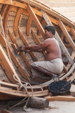 The poor man dressed in only one long loincloth repairs the wooden boat lying ashore. India, Varanasi, on February 6, 2014.