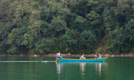 Family with the child, dressed in life jackets ride the rowboat on the Lake Pheva against the background of the wood. Pokhara, Nepal on March 3, 2017