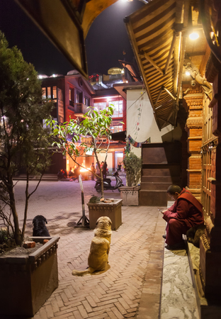 The Buddhist monk looks at the screen of the smartphone, sitting on stairs of houses in an environment of stray dogs on the square in front of a stupa Boudnath, Nepal, Kathmandu, on March 4, 2017