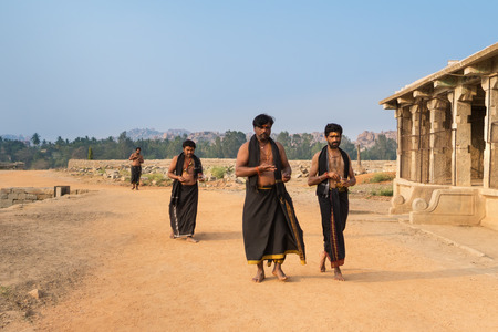 Hindu priests are from a caste Brahmins, dressed in black clothes, going to have a rest after the ritual ceremony in Virupakshas temple, in Hampi. Karnataka, India, on January 9, 2018 Editorial