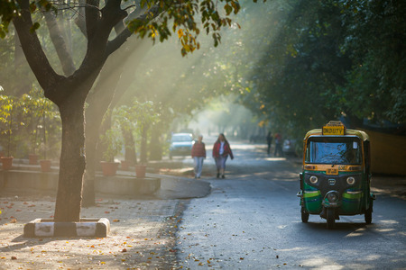 Lonely tuk-tuk moves on the road with trees, in the early solar morning. Beams of the sun make the way through branches of trees. India, New Delhi, on March 12, 2017