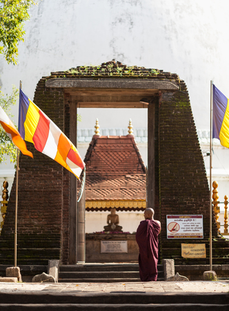 The Buddhist monk dressed in traditional Lankan monastic clothes standing in front of ancient gate which lead to Buddhas sculpture on an altar. Sri Lanka, Seruwawila, on February 2, 2017