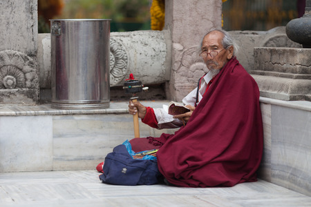 The old man - the Buddhist pilgrim, sits under the walls of Mahabodhi Temple, reads mantras and rotates a small wheel Editorial
