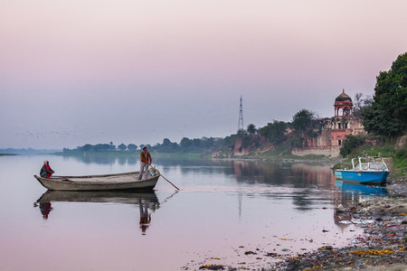Two persons float by the old wooden boat down the river Yamuna, near Taj Mahal. The coast has two police boats, against the background of an old structure in the Indian style and very polluted river bank. India, Agra, on February 9, 2014. Editorial