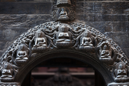 The stone arch in the Buddhist temple skillfully decorated by budda`s and bodhisattvas which are carved from a stone of black color. Stock Photo
