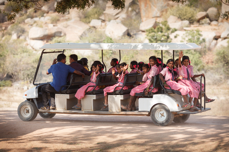 Young schoolgirls in pink identical dresses of a school uniform, going on the long electric vehicle - a golf-car towards sights, wave a hand and smile to passersby. India, Karnataka, vicinities of Hampi, on January 10, 2018