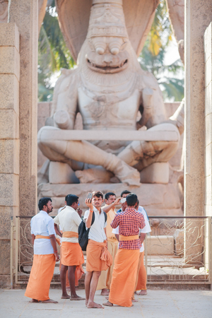The group of pilgrims - the Hindus dressed in orange clothes stands in front of Narasimhas monument - the angry embodiment of god Vishnu. The youngest of pilgrims takes a selfie against the background of a statue. India, Karnataka, Hampi, on January 10,