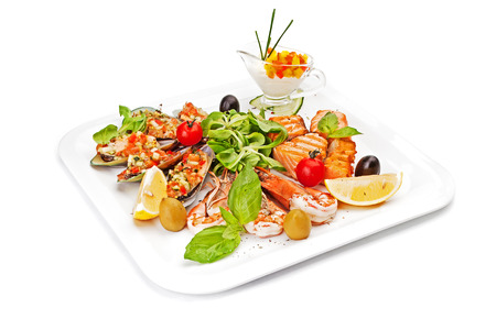 Pieces of fish fillet, fried and served on a white dish, served by leaves of salad, with olives, cherry tomatoes, an oiyster, arugula, a lemon segment, shrimps and tartlet with vegetables.
