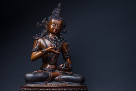 Vajrasattvas sculpture sitting with a dorje in one hand and a hand bell in another, on black background. Vajrasattva - a secret form of Buddha Samantabhadra.