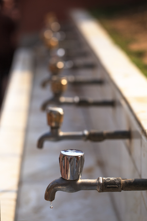 A sequence of faucet with copper handles in which water has reached a limit in hot sunny day, and only in one there was one drop of water. Stock Photo