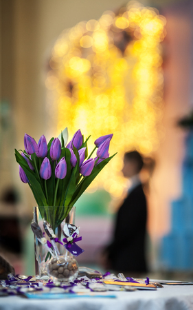 The bouquet of lilac tulips stands in a vase against the background of patches of light from bright garlands.