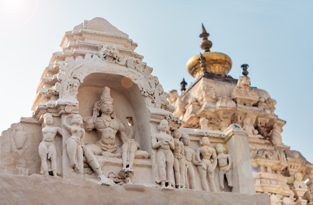 View of deity`s, roofs and tops of the Virupaksha temple complex against the background of the blue sky. Stock Photo