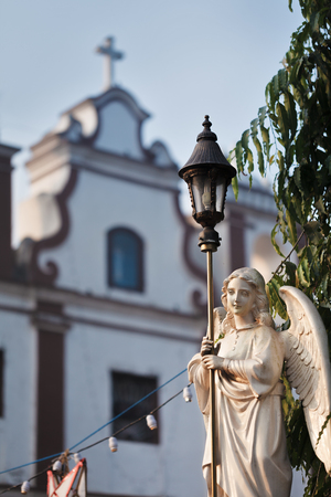 The angel in white with street lantern in dawn beams - a sculpture in front of the background of Catholic church.