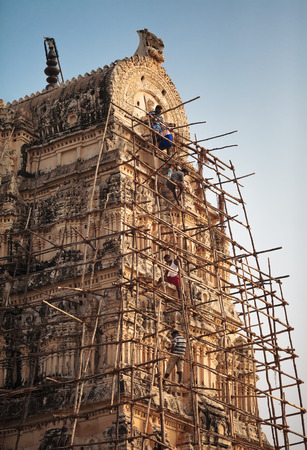 Five Indian workers, being on the woods from bamboo sticks, are engaged in restoration of decorative elements of one of buildings of the Virupaksha temple complex. India, Hampi, on January 9, 2018 Editorial