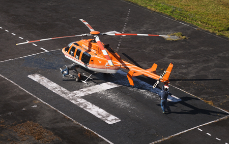 Helipad with thepreparation of the  orange helicopter for flight.
