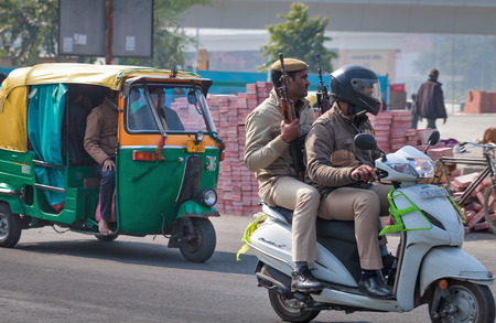 Two Indian police officers in city traffic, go on a small white motor scooter on streets of New Delhi. One of police officers holds two automatic machinegun. India, Delhi on January 19, 2018