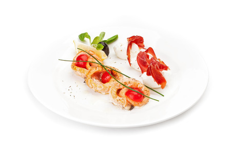 Dish sample at restaurant - thinly cut slices of air-dried meat on balls of mozzarella and the fried rings of fish fillet are served by a lemon segment. Isolated on a white background.