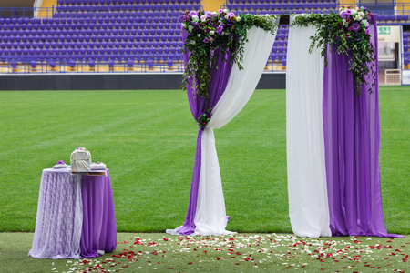 The decorative arch of violet color, for a ceremony of a solemn wedding is installed on the football field of stadium. Stock Photo