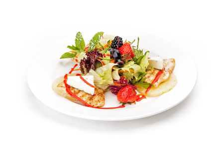 Dish sample at restaurant - lettuce leaves, chicken fillet, strawberry and blueberry with the French cheese and leaves of mint. It is isolated on a white background. Stock Photo