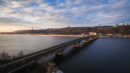 The winter aerial view on the bridge of the subway and the right coast of Dnieper, with Kiev-Pecherska Lavra and a monument