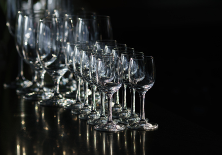Rows of the empty wineglasses and empty glasses for vodka, going to unsharpness, stands on a black background.