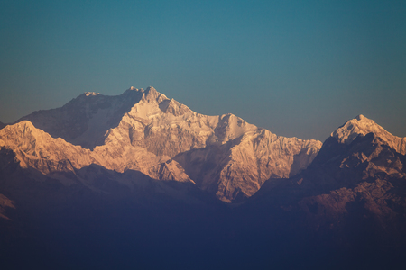 Mount Kanchenjunga peak with snow in beams of the  sunrise - the mountain, the third on height, in the world, on border of Nepal and the Indian state of Sikkim. Stock Photo
