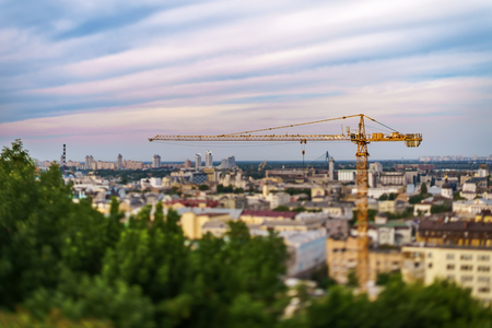 The crane in front of the background of Obolon district of the city of Kiev and striped clouds. The photo is executed with use of a lens tilt-shift.
