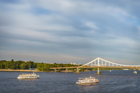 Two observing motor ships float down the river Dnieper, in windy weather, near the pedestrian bridge on Trukhanov the island, in the capital of Ukraine, the city of Kiev. Created with help tilt-shift lens.