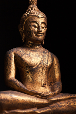 The gilded statue of smilin Buddha, in Southeast Asia style.  Isolated on black background.