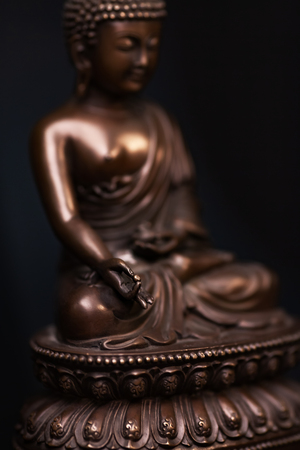 Defocused silhouette of Buddhas figure, brown color made of metal in a meditation pose with the hands keep a pearl of knowledge.