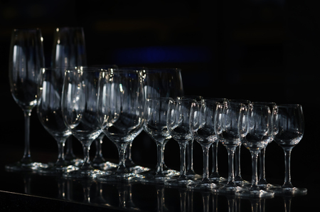 Rows of the empty wineglasses and empty glasses for vodka, stands on a black background. Stock Photo
