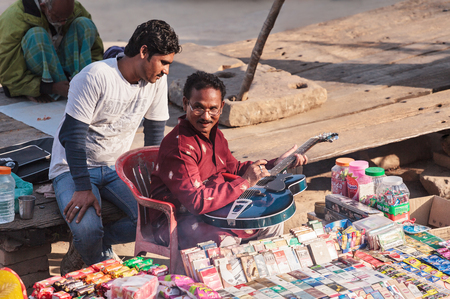 The street dealer in cigarettes sits with the friend on Ganges Embankment, and plays a semi-acoustic guitar. India, Varanasi, on February 6, 2014.