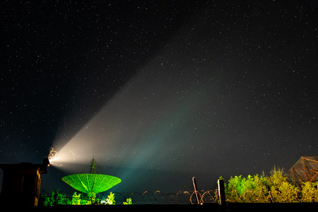 Beam of an old searchlight and line of barbed wire against the background of the big antenna of the radio telescope illuminated by green light under the night star sky. Stock Photo