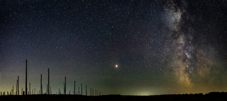 High posts in the field against the background of the star sky and the Milky Way with a bright star in the center.