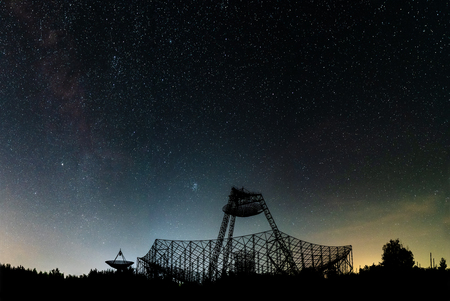 The group of antennas of the station of exploration of an ionosphere. A silhouette against the background of the night sky with glow and stars.