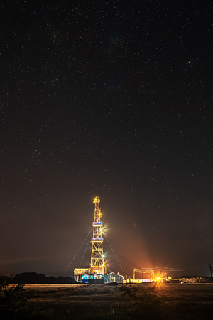 The derrick used for investigation of the gas field in beams of searchlights against the background of the star night sky.