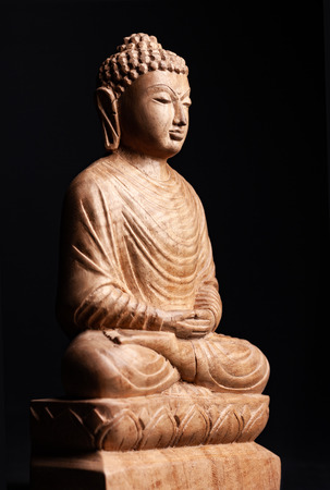 Buddha in a meditation pose of a whole lotus. Statue made of wood, isolated on a black background. Stock Photo