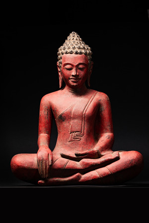 The statue of red Buddha, in Southeast Asia style. Isolated on black background. Stock Photo