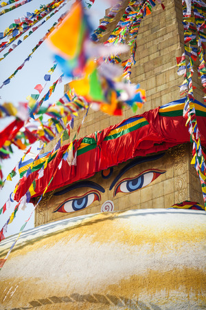 Buddhas eyes depicted on a buddhist stupa Boudnath, with many flutter flags of lunghta around.