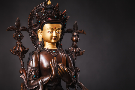 The Buddha of future - Buddha Maytereya`s figure in a dharmachakra mudra pose. The statue brown color made of metal on a dark background.