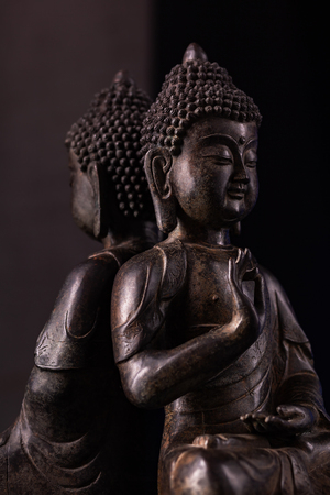 Buddha Shakyamunis figure in a meditation pose - vitarka mudra. The old statue brown color made of metal on a dark background.