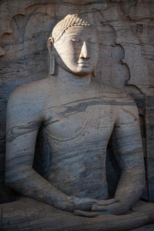The stone image of Buddha Gautama sitting in dhyana mudra, located near of Polonnaruwa - ancient capital of Sri Lanka.