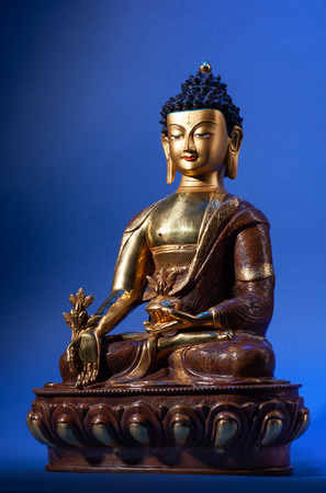 The gilded statue of Buddha Medicine in traditional clothes with flower of a medical plant of an arur.  Isolated on black background.