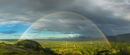 View of the rainy valley with the green forest and full double rainbow. Banco de Imagens
